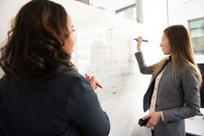 Free Two Women Standing In Front Of Rectangular Whiteboard Stock Images - 119666404