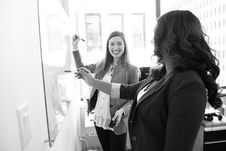 Free Two Smiling Woman Writing On Board Stock Photo - 119666420