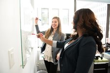 Free Two Women In Front Of Dry-erase Board Stock Image - 119666421