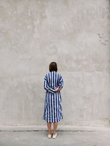 Free Woman Wearing Blue And White Striped Shirt Dress Facing Gray Wall Royalty Free Stock Photography - 119735217