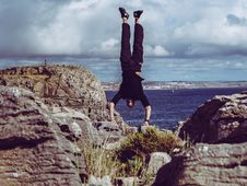 Free Man Wearing Black Dress Shirt And Burgundy Pants Hand Standing On Rock Formations Across Sea Royalty Free Stock Image - 119926226