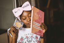 Free Girl Wearing White And Red Floral Shirt With Bow Headband Closing Her Eyes While Holding Body Blendz Book Royalty Free Stock Image - 119999896