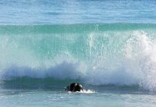 Surfer Ducking Under Large Breaking Wave Stock Image
