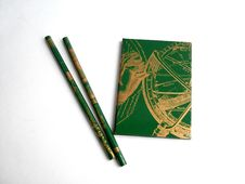 Green Notebook With Two Green Pencils On A White Background Stock Photo