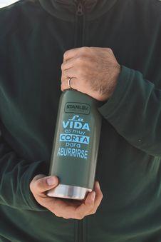 Free Person S Hand Holding Stanley La Vida Es Muy Corta Para Aburrirse Bottle Royalty Free Stock Photo - 120142555