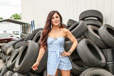 Free Woman In Blue And White Checkered Dress Standing In Front Of Stack Tires Stock Photos - 120142573