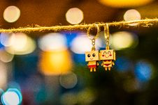 Free Two Man And Woman Wooden Couple Keychains Hanging On Rope Overlooking Bokeh Lights Royalty Free Stock Photos - 120142588