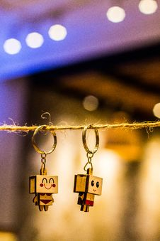Free Bokeh Photography Of Two Wood Block Man And Woman Figure Key Chains Hanging On Brown Thread Royalty Free Stock Image - 120142606