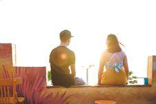 Free Man And Woman Sitting On Ledge Stock Photos - 120142623