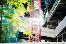Free Green Leafed Tree Beside Red Metal Trusses And Building Royalty Free Stock Photography - 120142677
