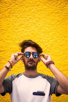 Free Man In White And Gray Shirt Wearing Sunglasses Against Yellow Wall Royalty Free Stock Photos - 120192608