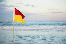 Free Red And Yellow Flag Standing Near Beach Stock Image - 120361051