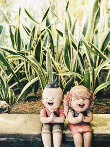 Free Boy And Girl Figurine Near Snake Plants At Daytime Stock Images - 120361154