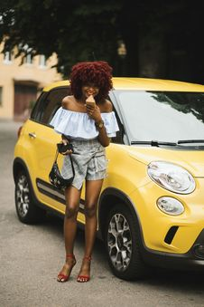 Free Woman Standing Beside Yellow Fiat 500l Stock Photos - 120462753