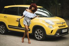 Free Woman Standing Near Yellow Fiat 500L Stock Images - 120462754