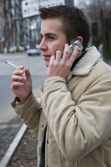 Young Smoker On The Phone Royalty Free Stock Photography