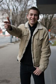 Young Smiling Guy Pointing With His Finger Stock Photography