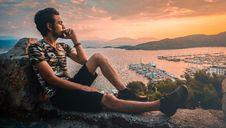 Free Man Sitting On Stone Under Orange Skies Royalty Free Stock Photos - 120524188