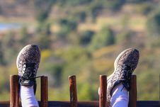 Free Person Wearing Black And Grey Nike Shoes Resting Feet On Wooden Fence Royalty Free Stock Photos - 120632478