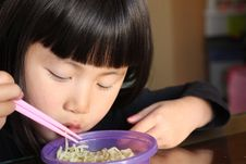 Asian Girl Eating Noodles Stock Image