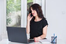 Free Cute Business Woman At Office Talking On The Mobile Phone And Working On Laptop Stock Photo - 124295920