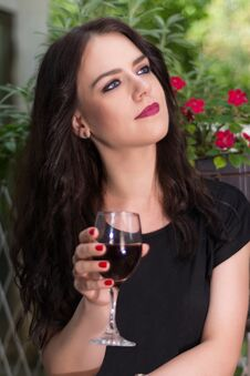 Free Young Beautiful Girl Holding Glass With Red Wine And Relaxing In Garden Royalty Free Stock Images - 124303389