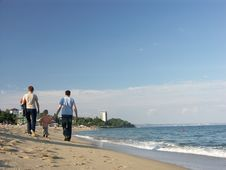 Free Family Stroll Along Seashore Stock Image - 1256861
