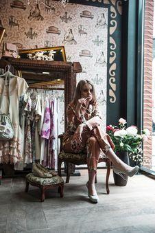 Free Woman Sitting On Armchair Near Glass Window And Flower Arrangement Stock Photos - 126175913