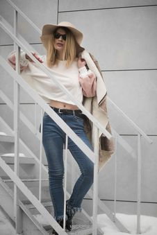 Free Woman In White Crew-neck Long-sleeved Crop Top And Blue Denim Fitted Jeans Outfit Standing On White Metal Stairs Beside White Wall Stock Images - 126176184
