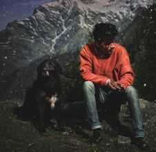 Free Man Sitting On Rock Next To A Dog Royalty Free Stock Photography - 126176547