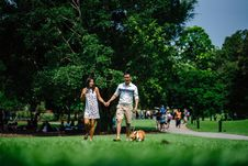 Free Woman And Man Holding Hands Beside Brown Dog While Walking On Green Grasses Surrounded By Green Leafed Trees Royalty Free Stock Photos - 126176708