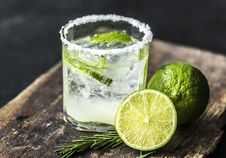 Free Sliced Lime Fruit Near Clear Drinking Glass With Lime Juice On Brown Wooden Plank Stock Image - 126177751