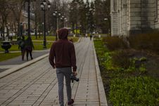 Free Man Wearing Hoodie Walking On Concrete Pathway Holding Dslr Camera Near Concrete Building Royalty Free Stock Photography - 126178107