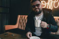 Free Smiling Man Sitting Near Table Holding Ceramic Mug Inside Room Royalty Free Stock Photography - 126178147