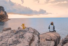 Free Person Sitting On Cliff Near Body Of Water Royalty Free Stock Photos - 126178728