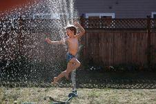 Free Boy Jumping On Water Sprinkler Royalty Free Stock Photos - 126178868