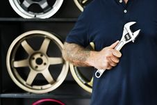 Free Person Holding Silver Crescent Wrench Behind Vehicle Wheels Stock Photos - 126178973