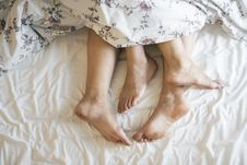 Free Two People Laying On A Bed Covered With A Floral Comforter Stock Photos - 126179103