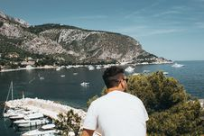Free Man Wearing White Shirt And Sunglasses In Front Of Boats And Mountain While Looking Right Side Under Blue Sky Stock Photo - 126179110