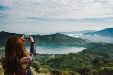 Free Woman Taking Photo Of Green-covered Mountain Stock Image - 126179321