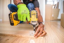 Free Person Using Dewalt Cordless Impact Driver On Brown Board Royalty Free Stock Images - 126179549