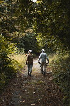 Free Two Men Walking On Way In Between Trees Stock Image - 126179611