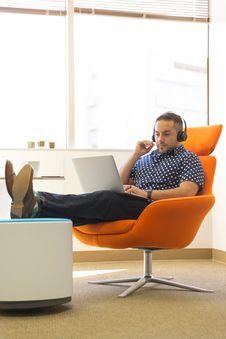 Free Man Wearing Headphones Sitting On Orange Padded Chair While Using Laptop Computer Royalty Free Stock Photos - 126179688