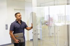 Free Man Standing Next To Glass Door Stock Photo - 126179760