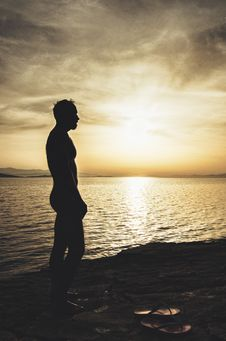 Free Topless Man On Sand Near Body Of Water During Sunset Stock Photo - 126179790