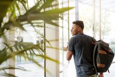 Free Man Looking Outside Window Carrying Black And Brown Backpack While Holding His Hand On Window Stock Photography - 126179822