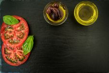 Free Sliced Tomatoes With Basil Leaves And Two Cooking Oils On Black Wooden Surface Stock Photos - 126179933