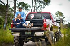 Free Man And Woman Sitting On Back Of Pickup Truck Royalty Free Stock Photography - 126180227