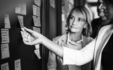 Free Grayscale Photography Of Woman Looking At Woman Picking Up Sticky Note On Board Stock Photo - 126180500