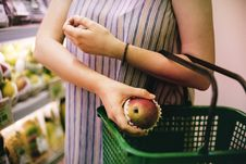 Free Woman Putting Red Apple On Green Shopping Basket Royalty Free Stock Image - 126180576